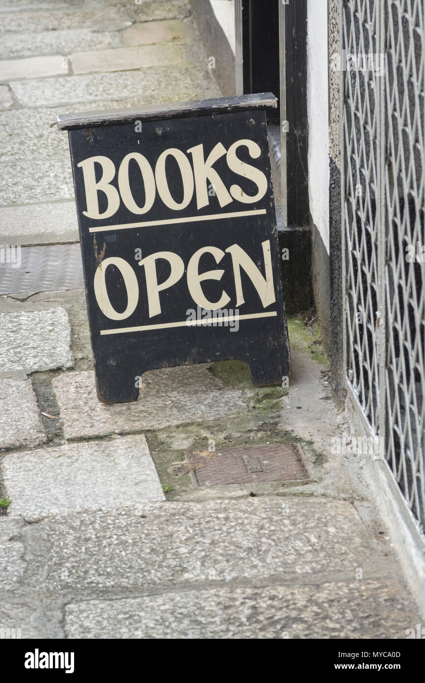 Open sign at a bookshop in Truro, Cornwall  Metaphor - book trade