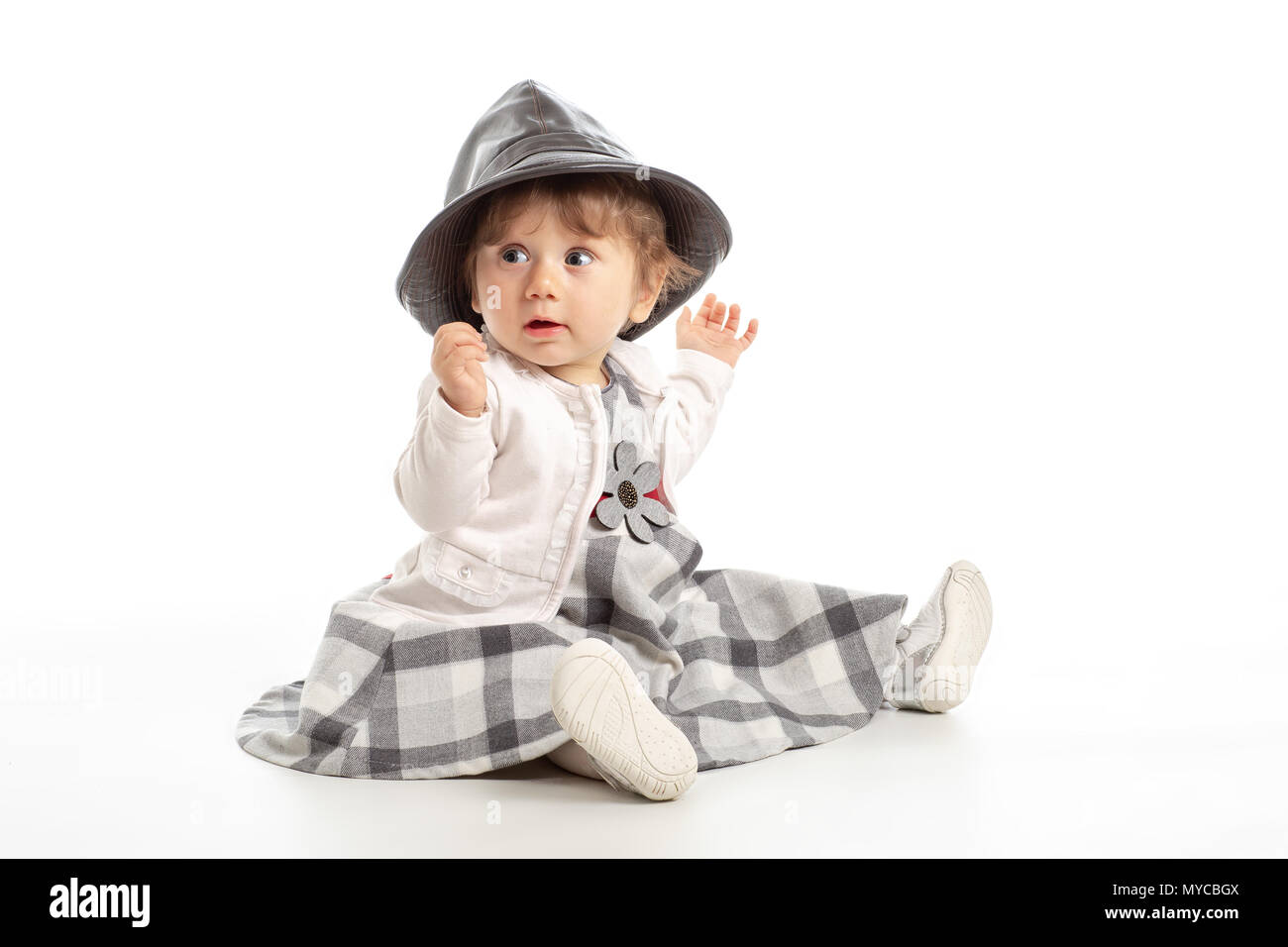 5ecd1a56f660e Elegant Happy baby girl 1 year old sitting on the studio floor with black  leather hat
