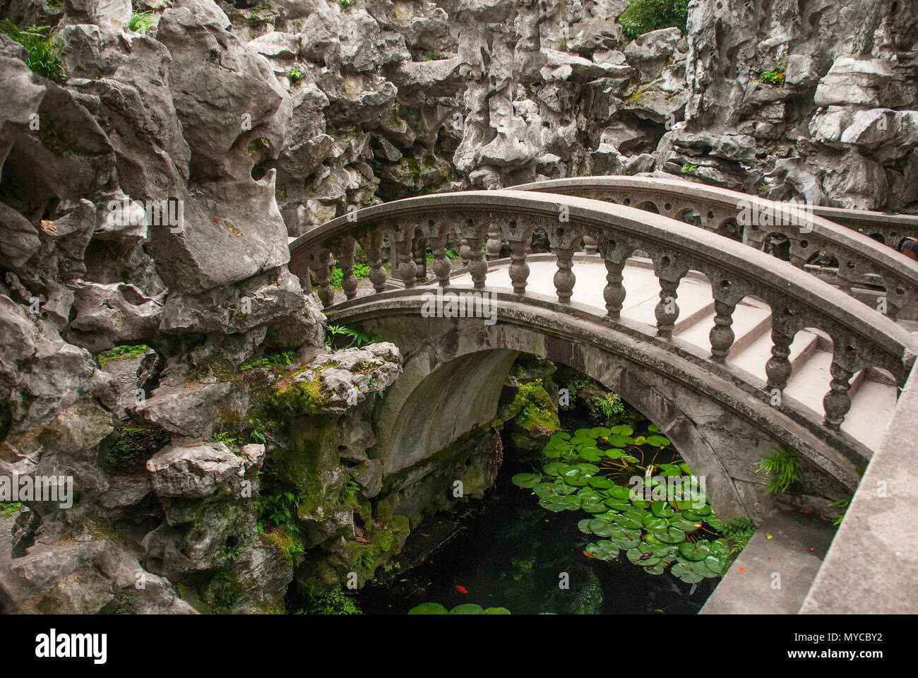 ancient stone arch bridge over pond inside Chinese rock garden Stock ...