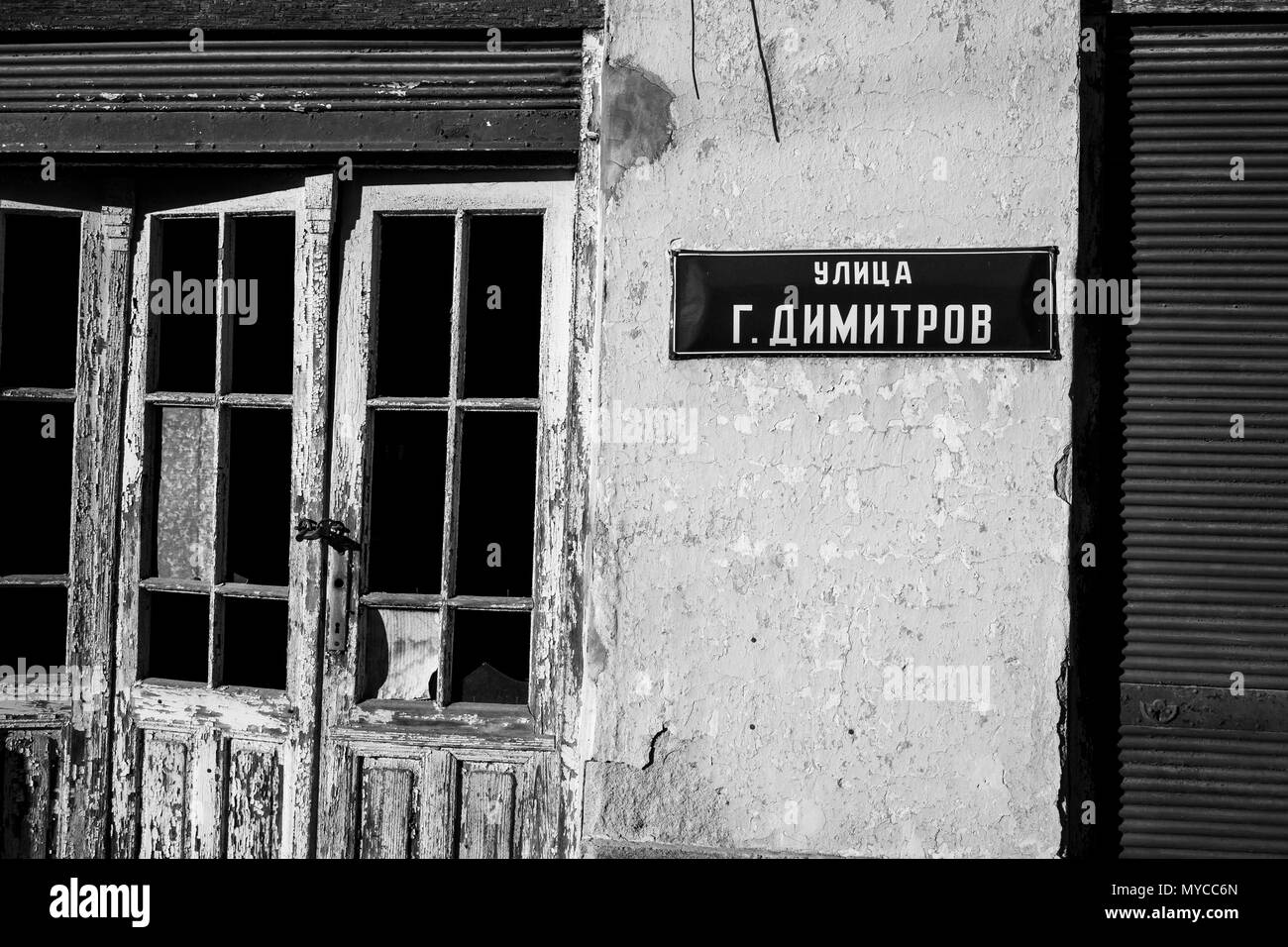 Street tinplate sign in Cyrillic G.Dimitrov on abandoned ruined house in small Bulgarian village, black and white image - Stock Image