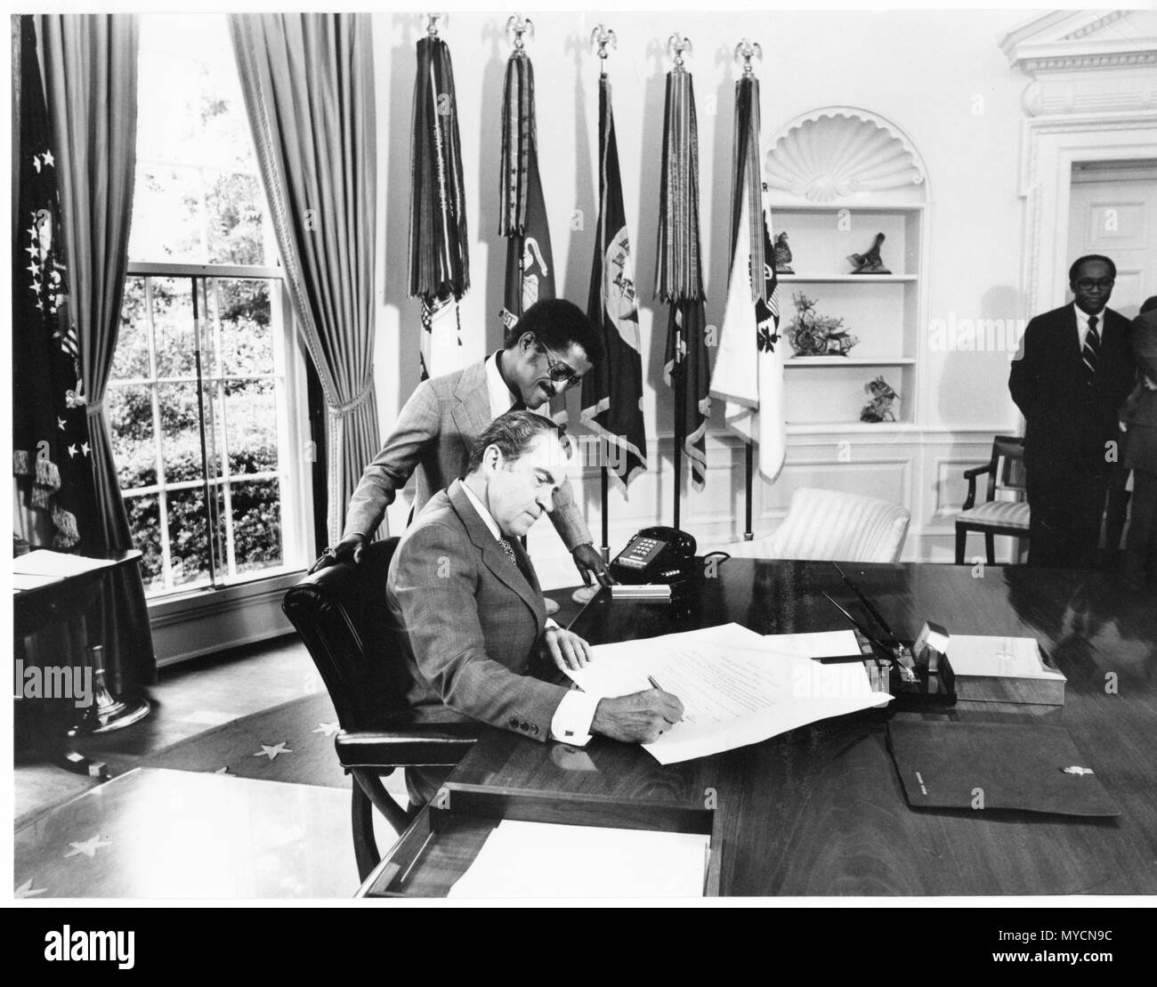 Richard Nixon Watchmen: President Richard Nixon Signing A Paper While Sammy Davis