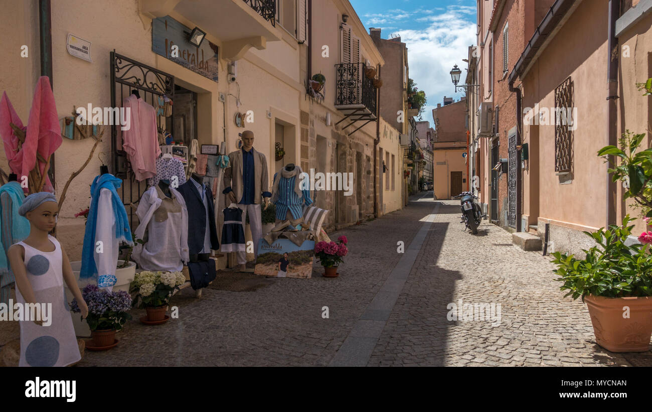 Streets of Olbia old town with local clothes shop displaying goods outside, Sardinia - Stock Image