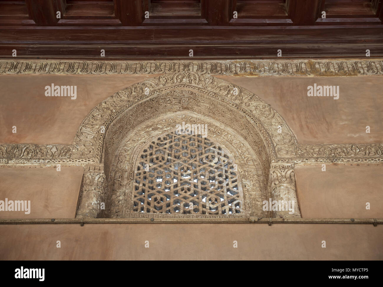 Perforated arched stucco window decorated with geometrical patterns and calligraphy at Ibn Tulun mosque, Old Cairo, Egypt - Stock Image