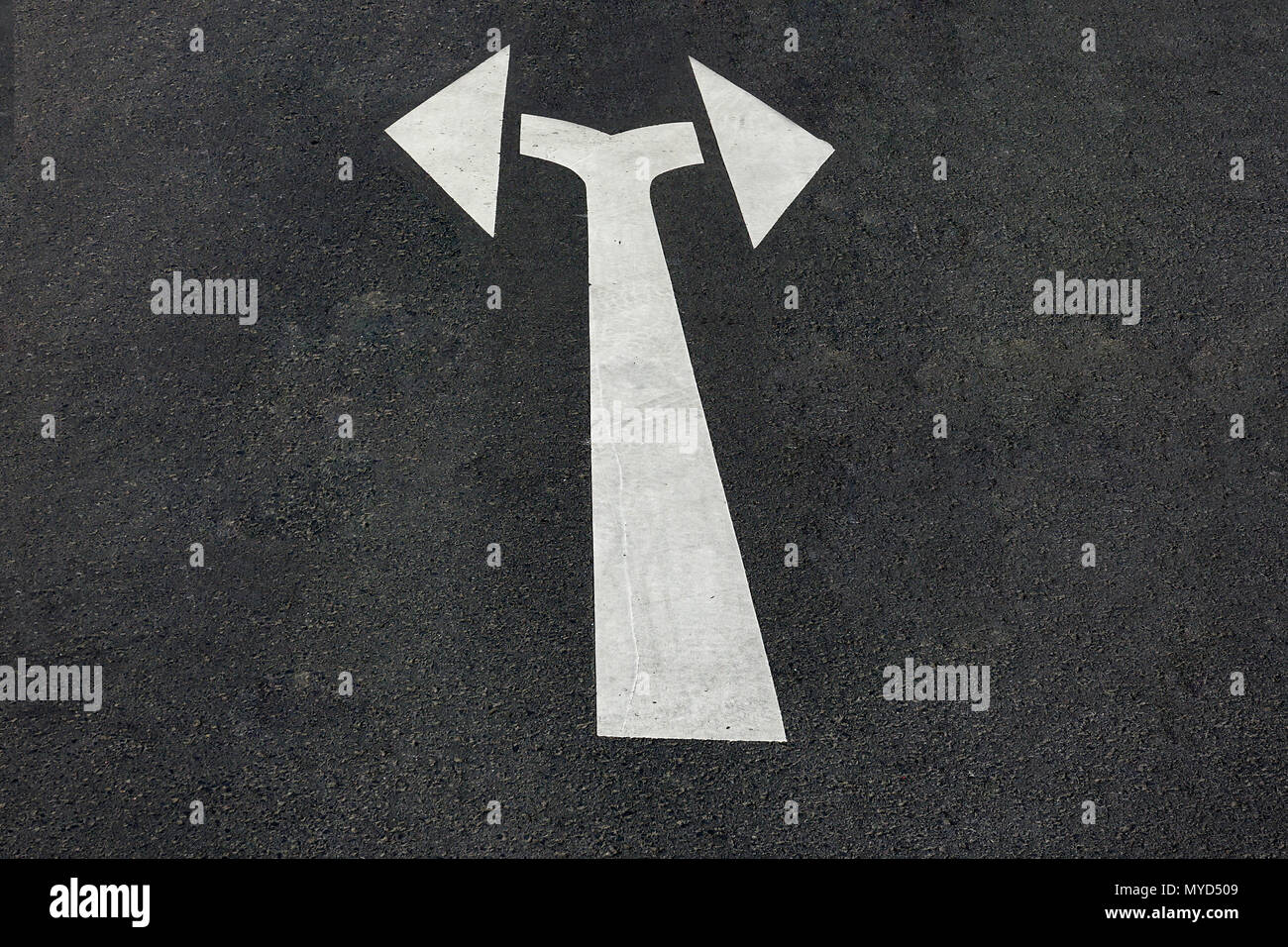 Double pointing arrow painted on the asphalt on a street with left and right pointing arrows indicating a turn conceptual of choices, opportunities an Stock Photo