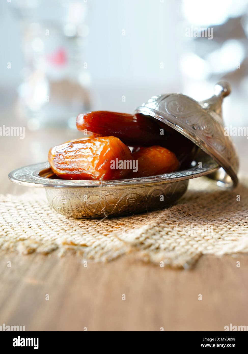 Fresh fruit dates in a silver metal bowl on a piece of sackcloth on walnut wooden table - Stock Image
