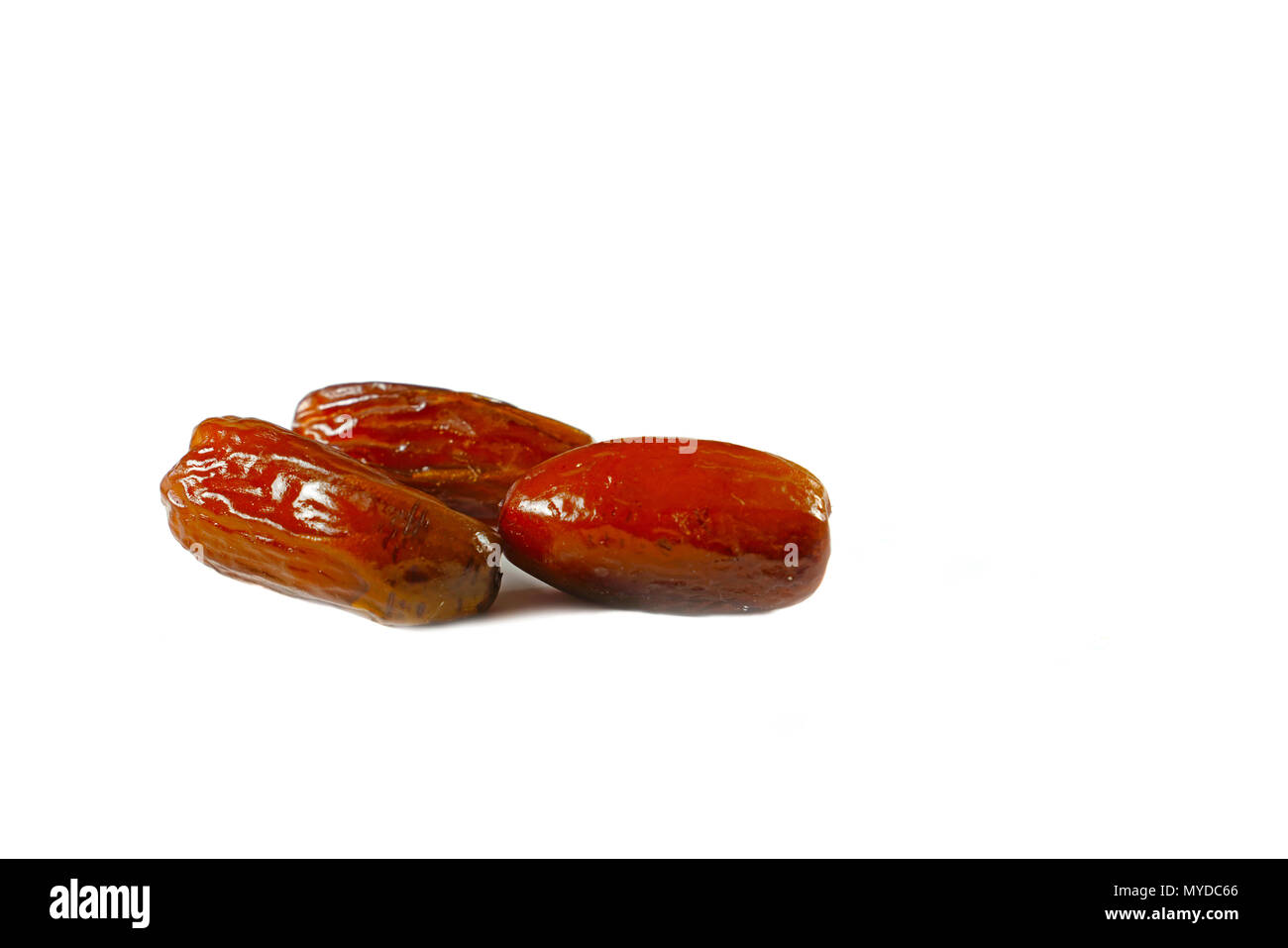 Three dried date fruit on isolated white background - Stock Image