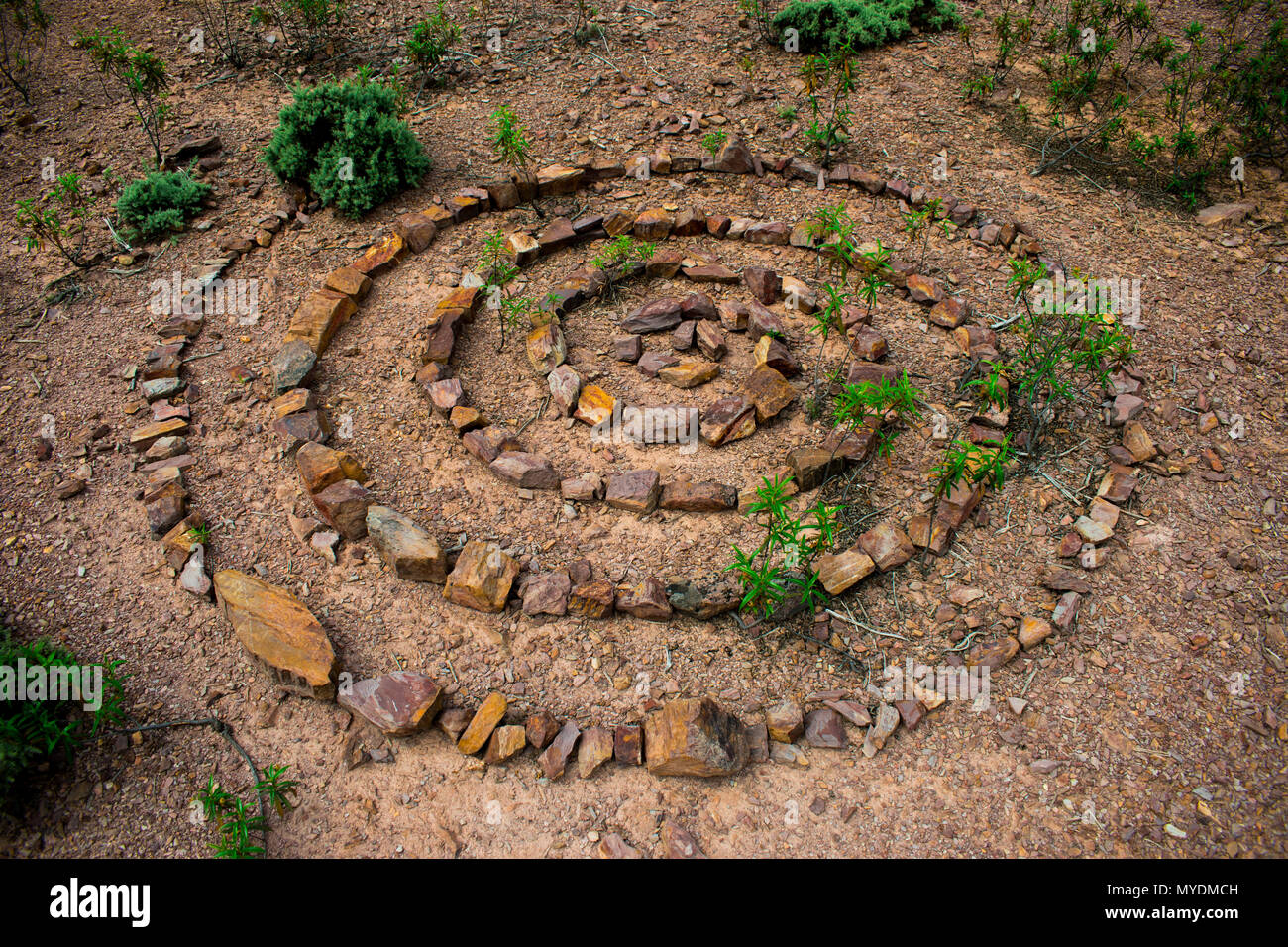 Stone spiral made up of lots of individual rocks on a dry stony floor with green plants growing up through the spiral of stones. - Stock Image