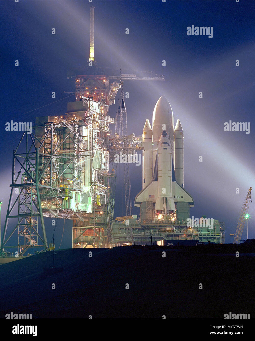 A timed exposure of the Space Shuttle, STS-1, at Launch Pad A, Complex 39, turns the space vehicle and support facilities into a night- time fantasy of light. Structures to the left of the Shuttle are the fixed and the rotating service structure. - Stock Image