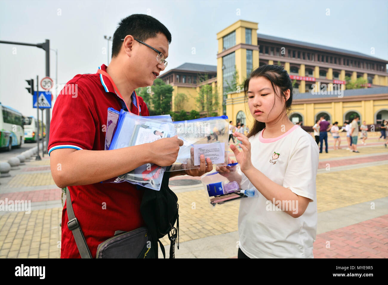 Chengdu, China's Sichuan Province. 7th June, 2018. A teacher distributes ID cards and stationery to examinees at an exam venue in Chengdu, capital of southwest China's Sichuan Province, June 7, 2018. About 9.75 million students have registered for the national college entrance examination, which takes place from June 7 to 8. Credit: Jiang Hongjing/Xinhua/Alamy Live News - Stock Image