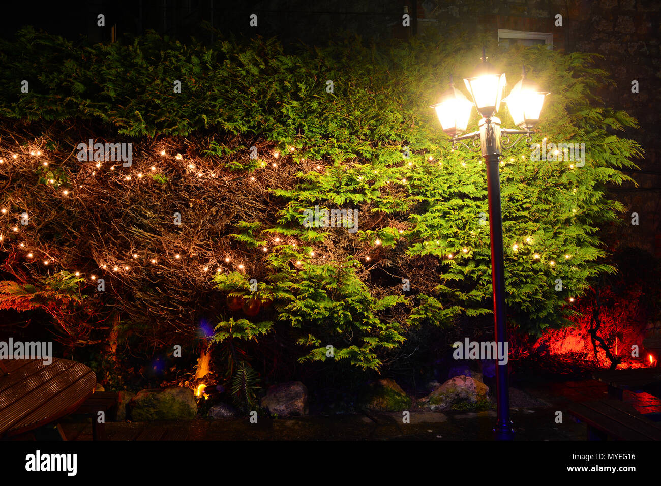 Fairy Lights And An Old Street Lamp Illuminates Bushes And A Picnic Table  In An Oudoor Garden At Night.