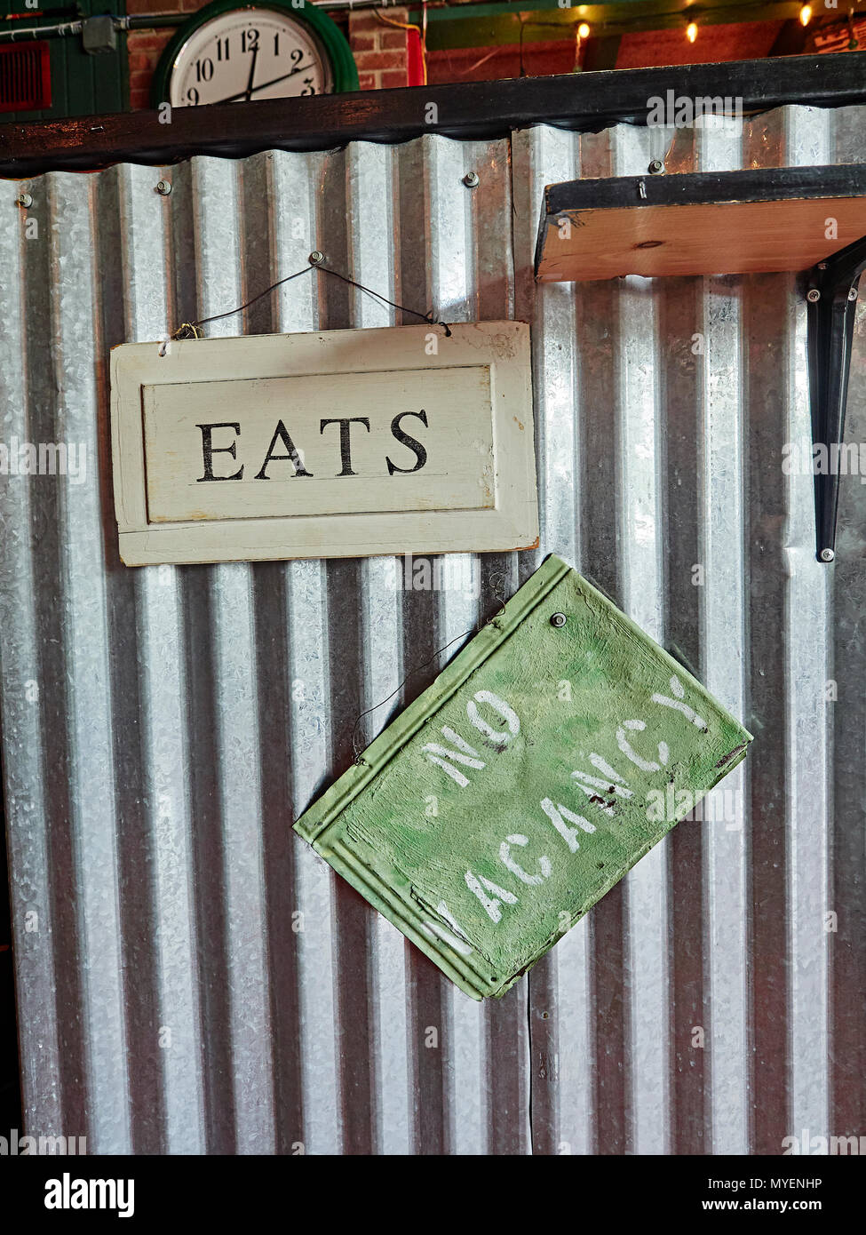Eats and No Vacancy sign or signs hanging on restaurant wall for interior design in a hip college town restaurant in Auburn Alabama, USA. - Stock Image