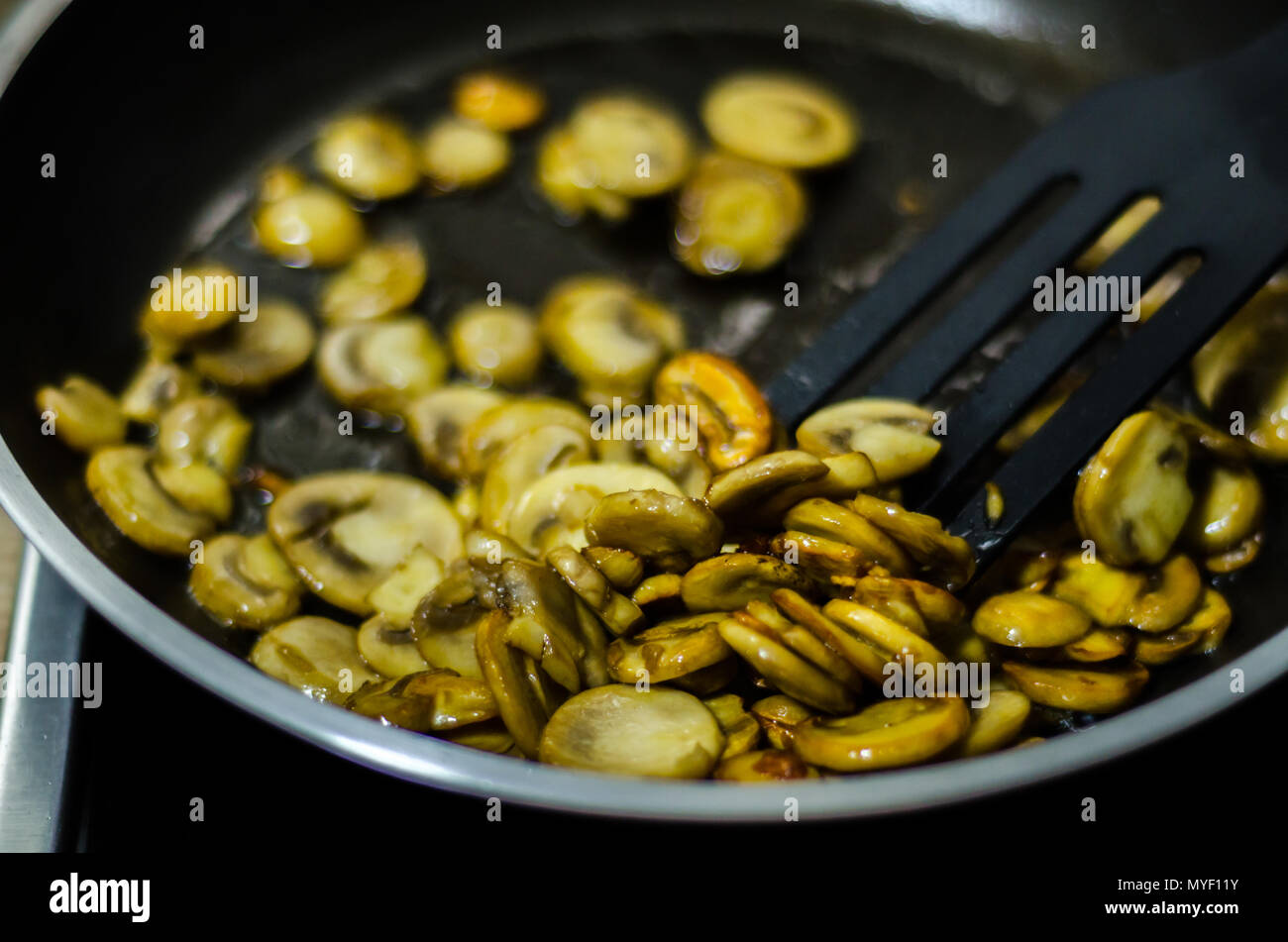 sliced mushrooms fried in butter in a pan, vegetarian dish, healthy snack - Stock Image