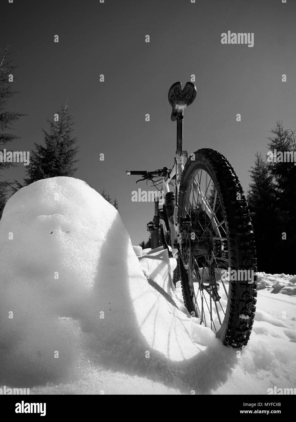 Close wide view to mountain bike stays in snow. Winter snowy mountains with road between trees. - Stock Image