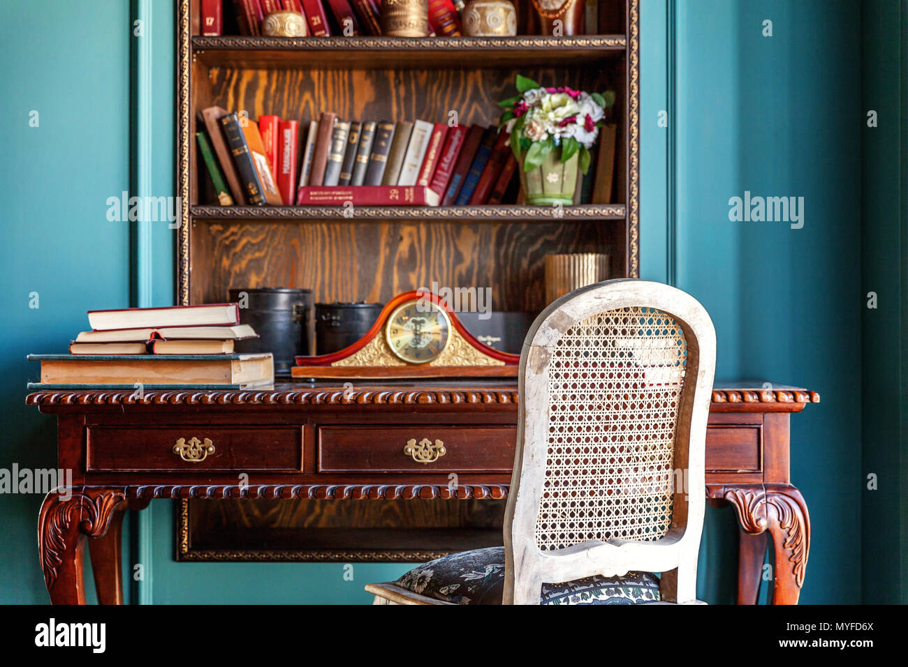 Luxury classic interior of home library. Sitting room with bookshelf, books, table and chair. Clean and modern decoration with elegant furniture. Educ - Stock Image