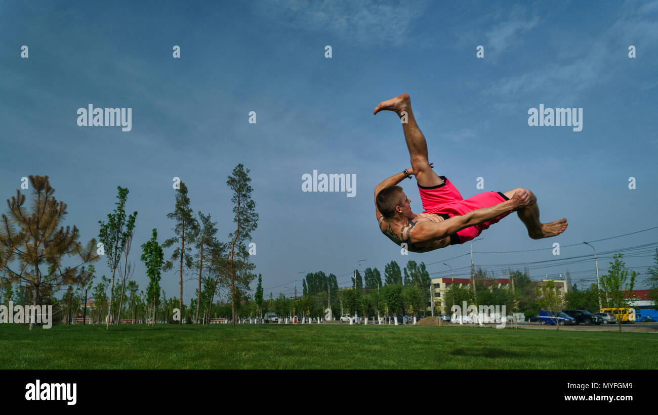 Tricking on lawn in park. Man does somersault ahead. Martial arts and parkour. Street workout. - Stock Image