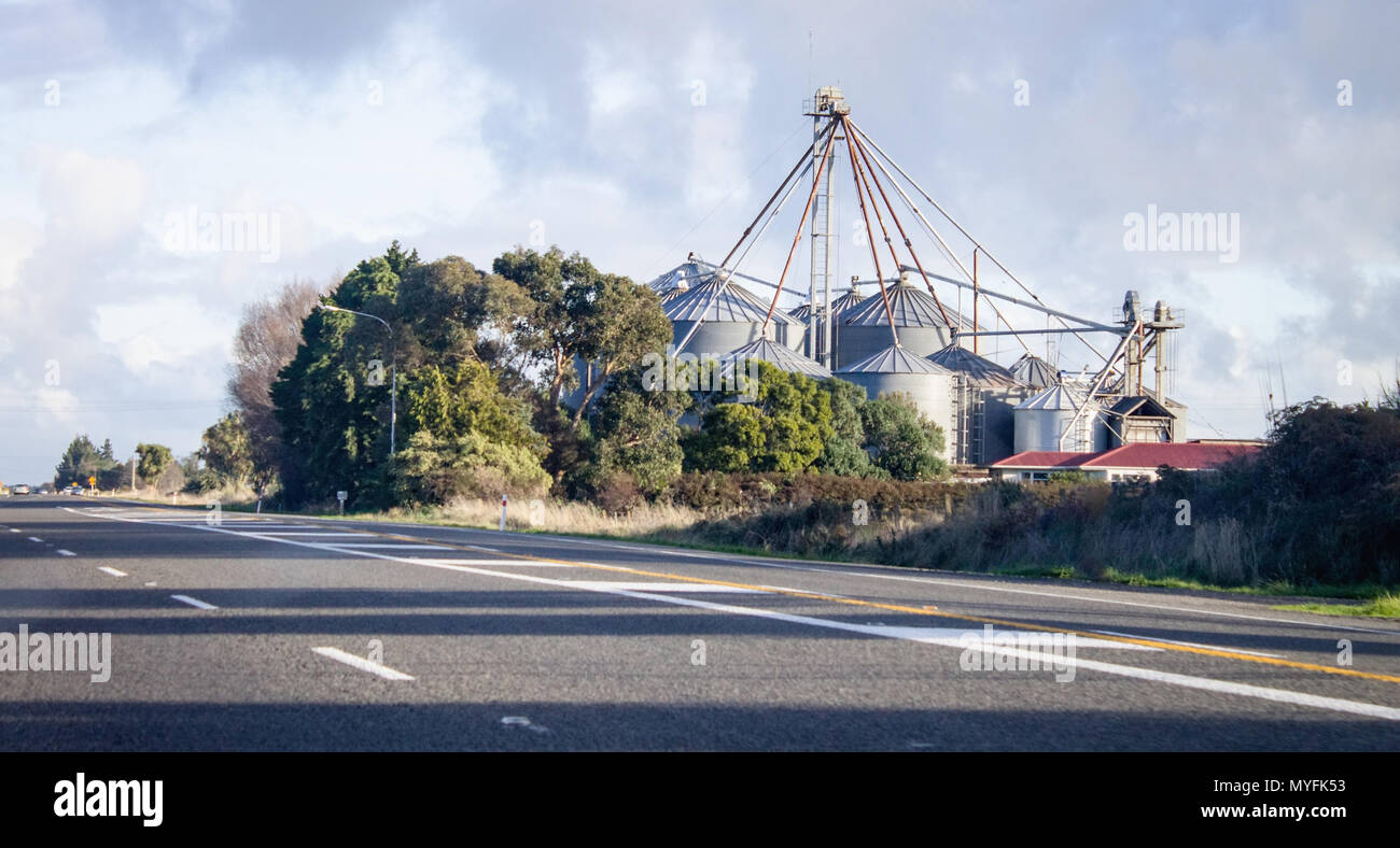 Rural State Highway road passing by grain silos in New Zealand. - Stock Image