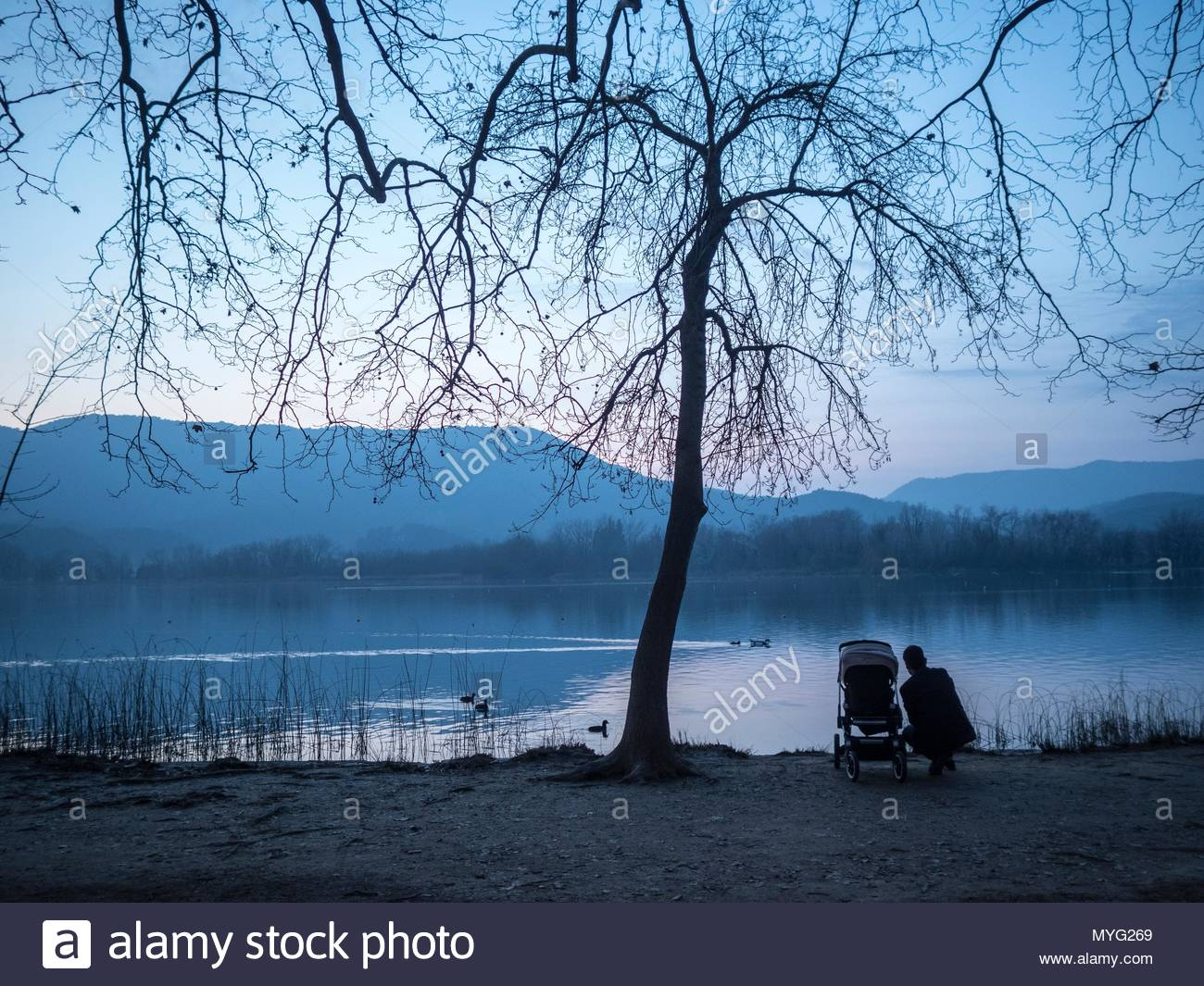 A parent with a baby stroller await sunset at the lake shore. - Stock Image