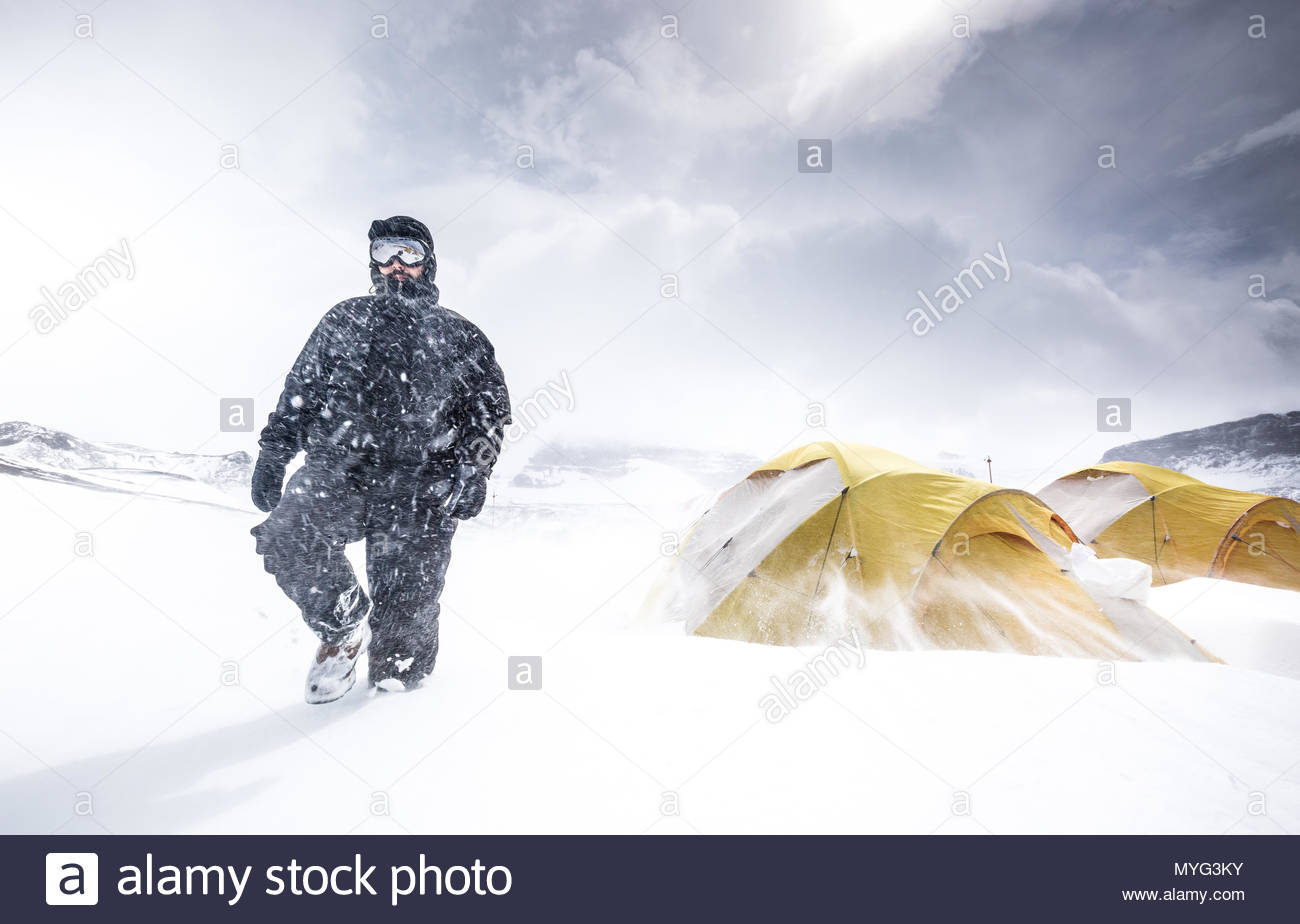 A researcher walks next to his tent during a snowstorm with strong winds in Antarctica. - Stock Image