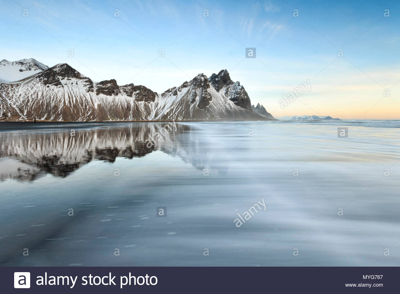 Vestrahorn mountain rises above the gentle surf of the North Atlantic. - Stock Image
