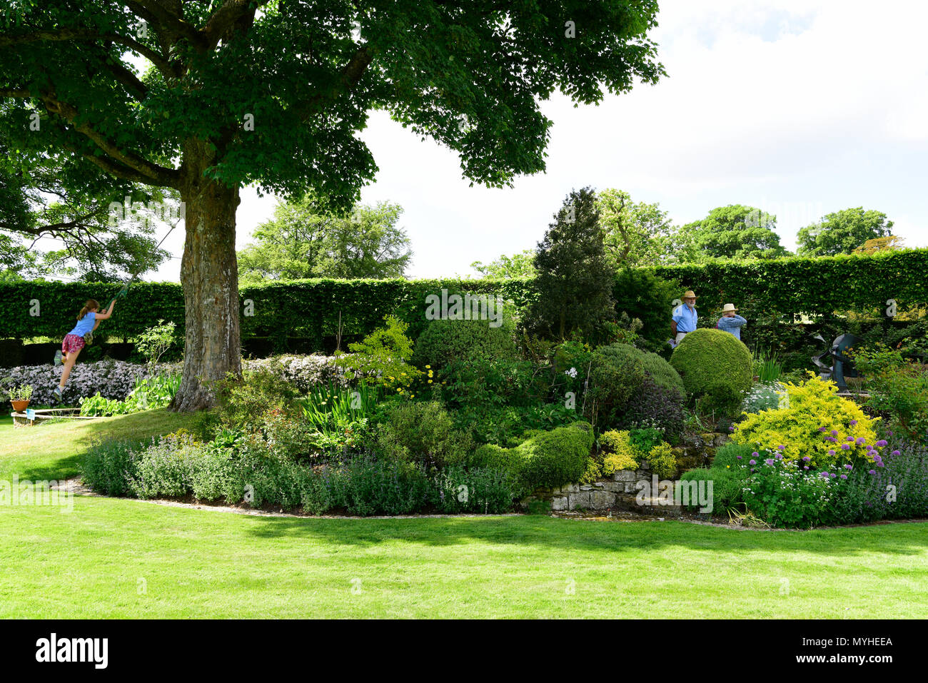 Visitors to the Open Gardens at Newton Valence perusing an English courtyard garden, Newton Valence, near Alton, Hampshire, UK. 20.05.2018. - Stock Image