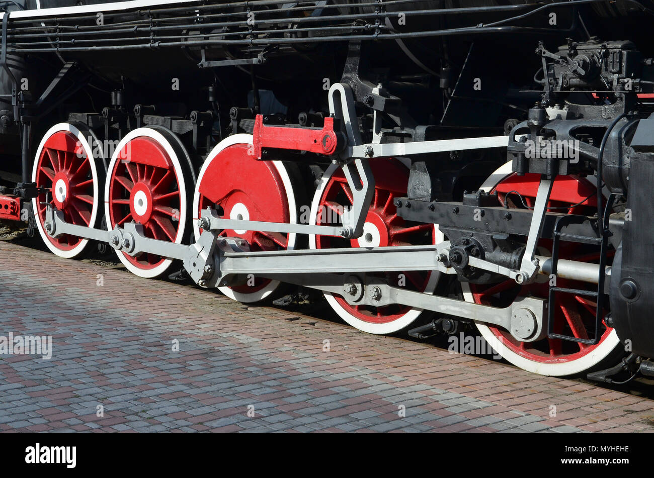 Wheels of the old black steam locomotive of Soviet times. The side of the locomotive with elements of the rotating technology of old trains Stock Photo