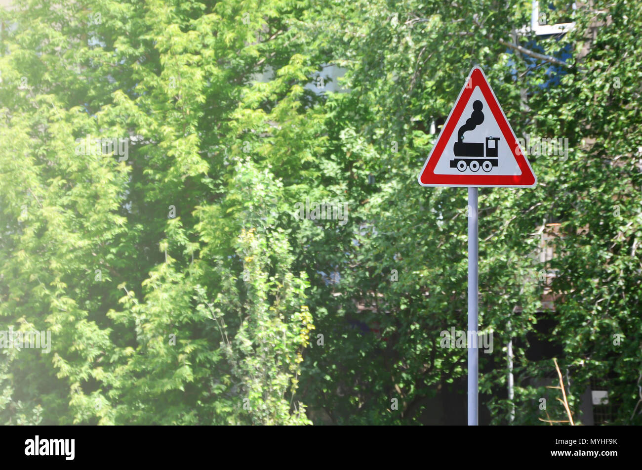 Triangular road sign with a picture of a black locomotive on a white background in a red frame. Warning sign for the presence of a railway crossing th - Stock Image