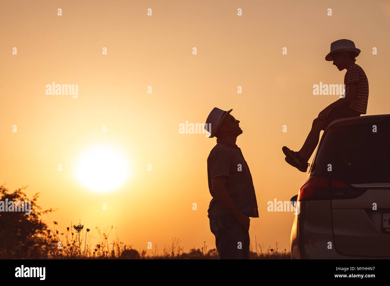 Father and son playing in the park at the sunset time. People having fun on the field. Concept of friendly family and of summer vacation. - Stock Image