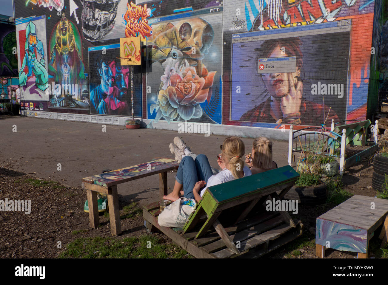 4f3d4265cc4 Visitors relaxing in the sunshine with graffiti art painting on walls of  the Nomadic communal gardens