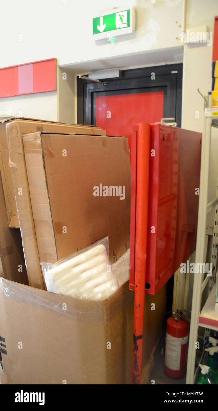 Goods in a shop block the fire escape door and als blocks the fire hose locker. - Stock Image