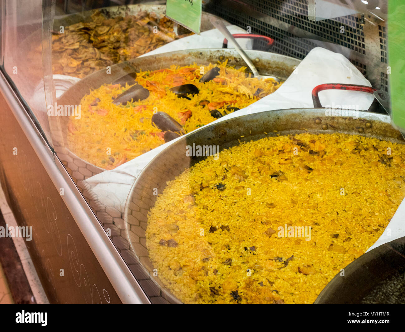 Huge pots with various types of paella on a counter at the central market in Valencia, Spain Stock Photo