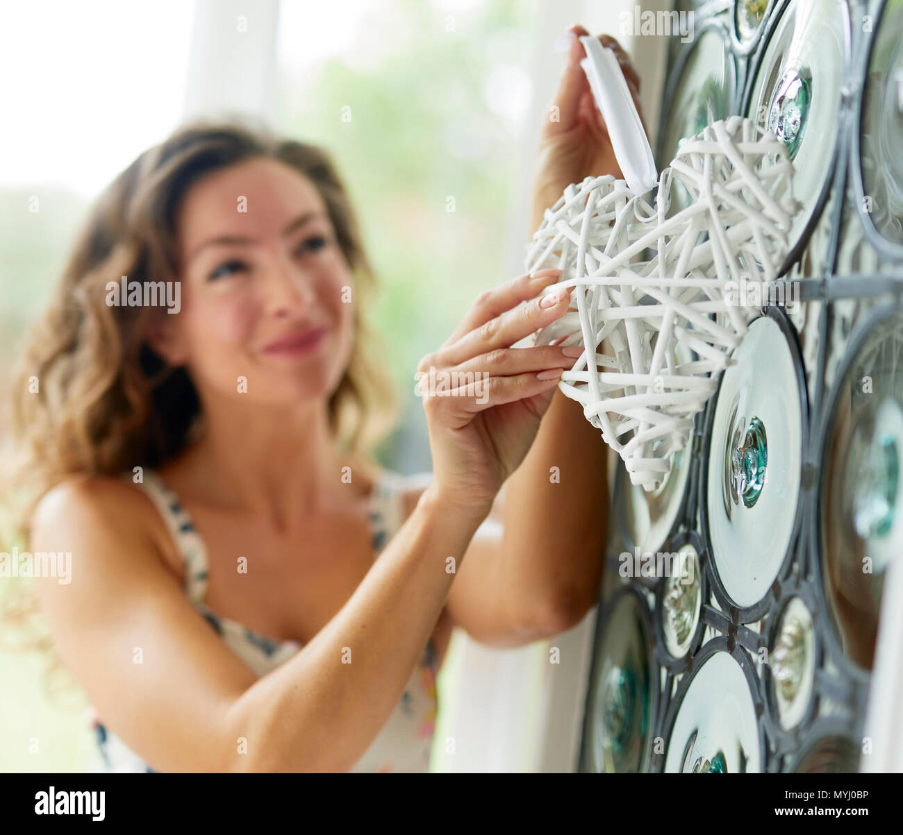 Woman hanging decorations on front door - Stock Image