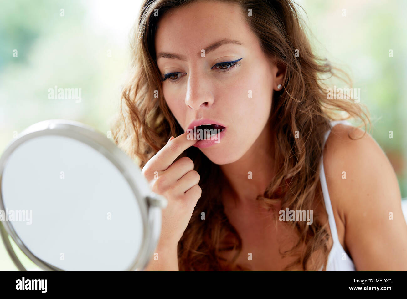 Girl looking in her mouth - Stock Image