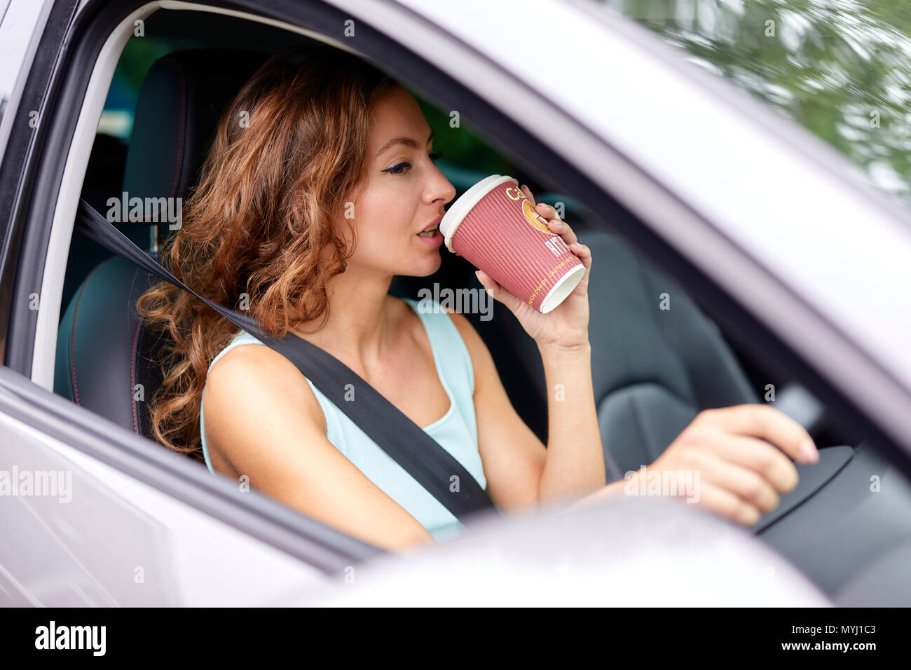 Woman drinking coffee whilst driving - Stock Image