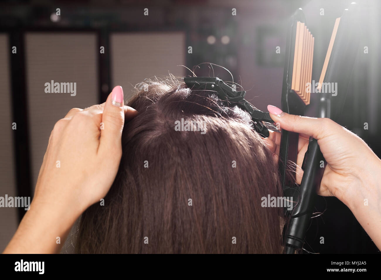 hairdresser clipping hair of a model - Stock Image