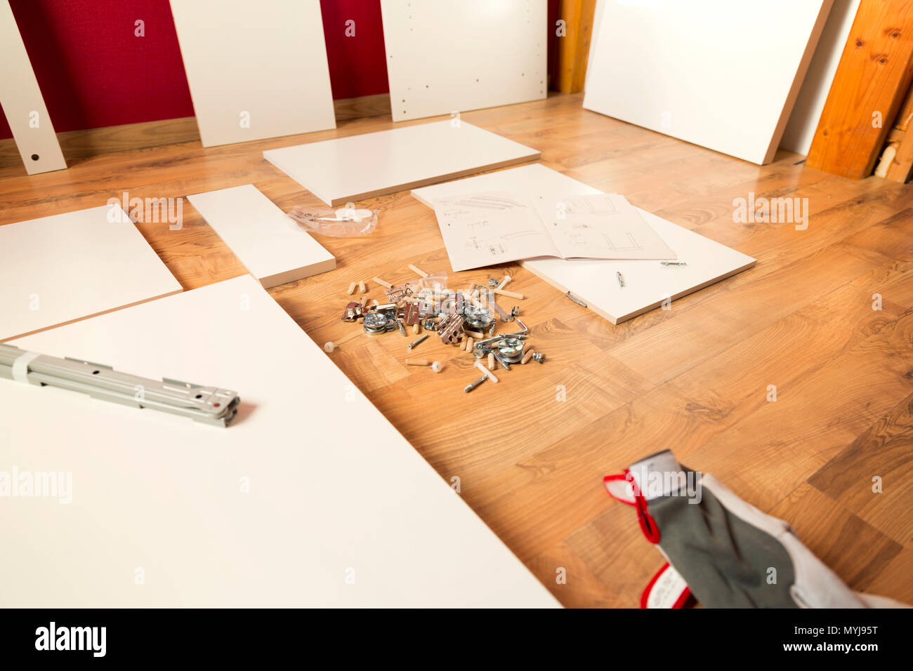 Assembling new wooden bed by hand in room. Man putting together new furniture. - Stock Image