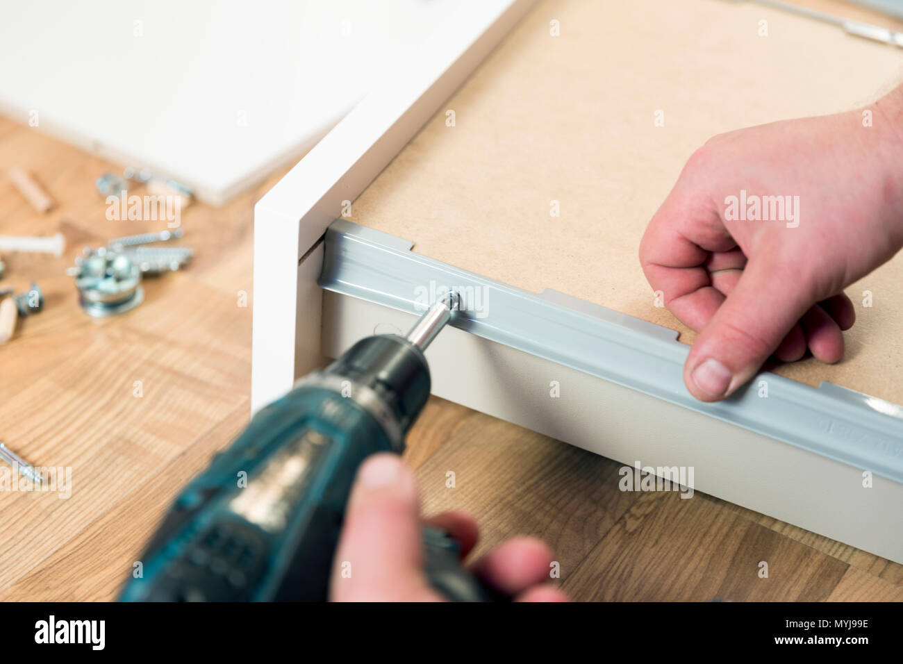 Assembling furniture from chipboard, using a cordless screwdriver - Stock Image
