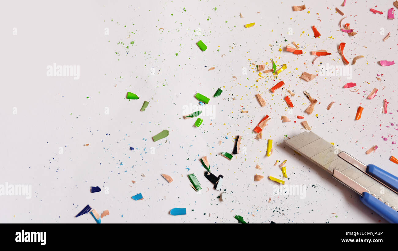 Flat lay of cutter blade with colorful pencil shavings scattered around it. - Stock Image