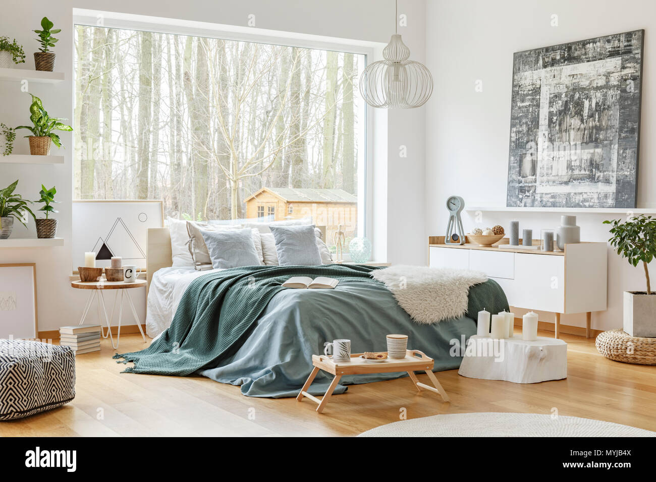 Green and blue bedsheets on bed in bedroom interior with painting on ...
