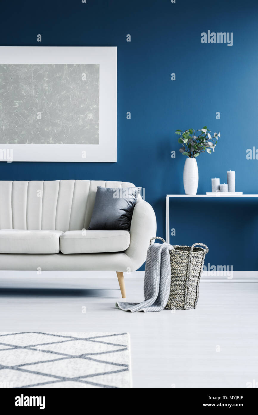Grey blanket in wicker basket placed next to a bright couch in blue sitting room interior with modern painting