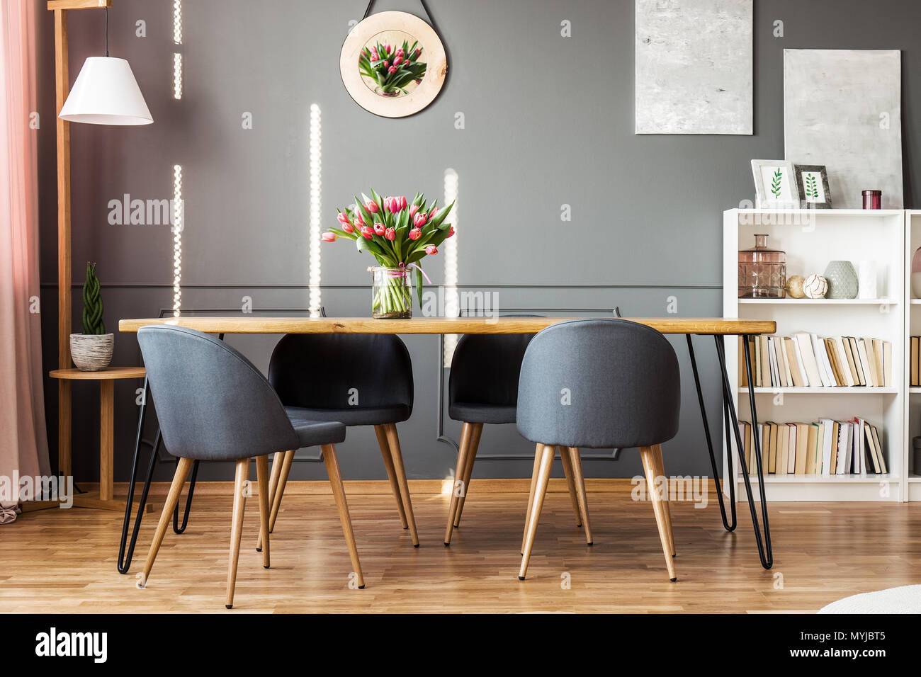 Wooden Dining Table Grey Chairs Bookshelf And Pink Tulips In Dining Room Interior Stock Photo Alamy