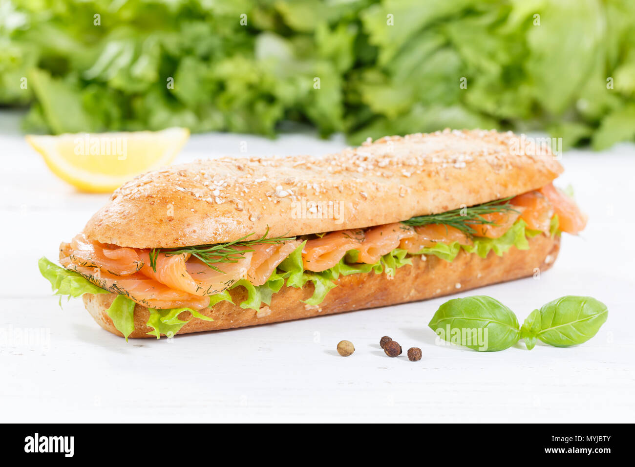 Sub sandwich whole grains baguette with smoked salmon fish on wooden board wood - Stock Image