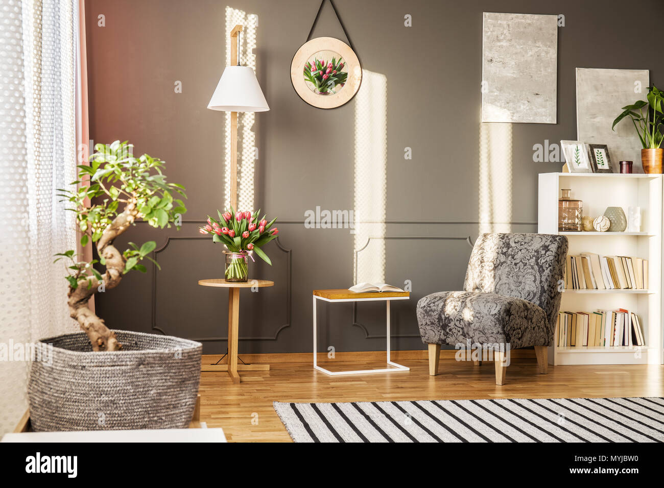 Bonsai Tree In A Fabric Pot Cover Tulips On Wooden Table Bookshelf And Patterned Armchair Living Room Interior