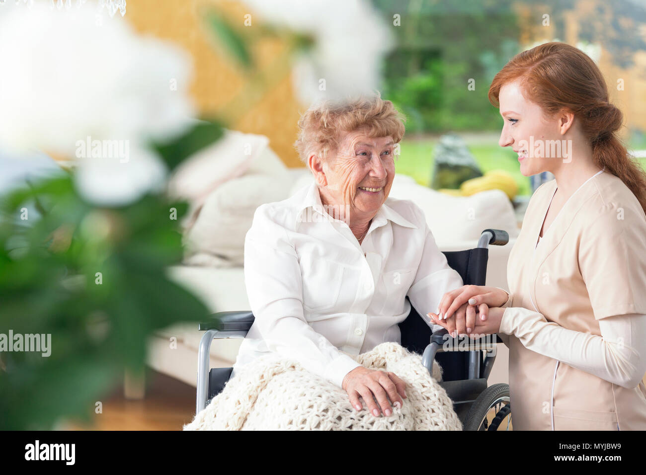 Smiling senior woman in a wheelchair and friendly nurse - Stock Image