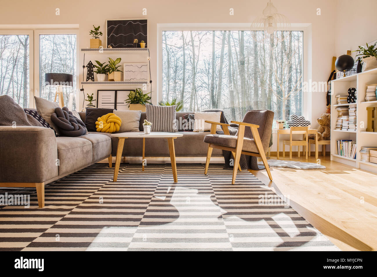 Low angle of warm bright living room interior with armchair at wooden table next to corner sofa - Stock Image