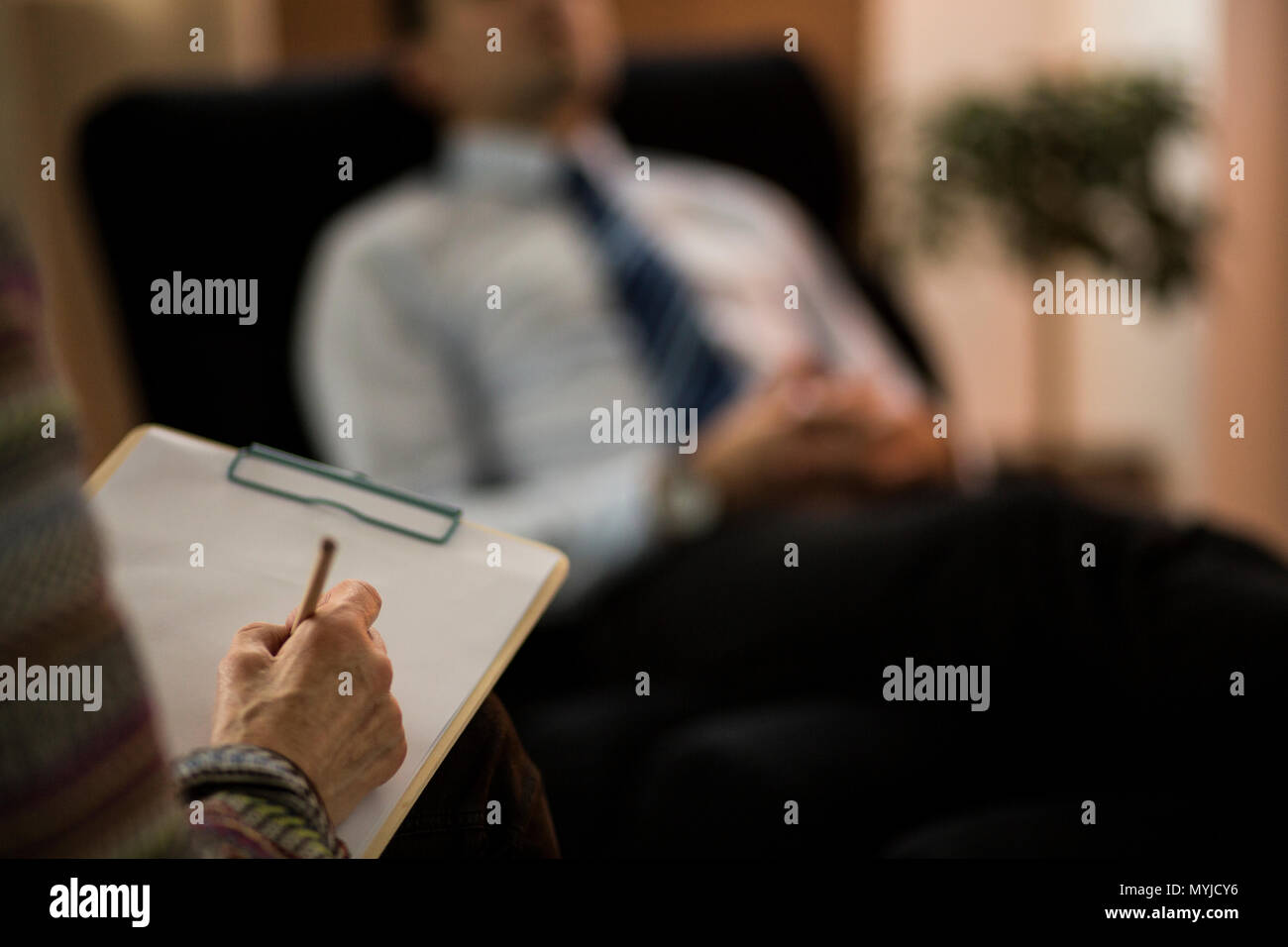 Close-up of psychotherapist writing a diagnosis while analyzing patient Stock Photo