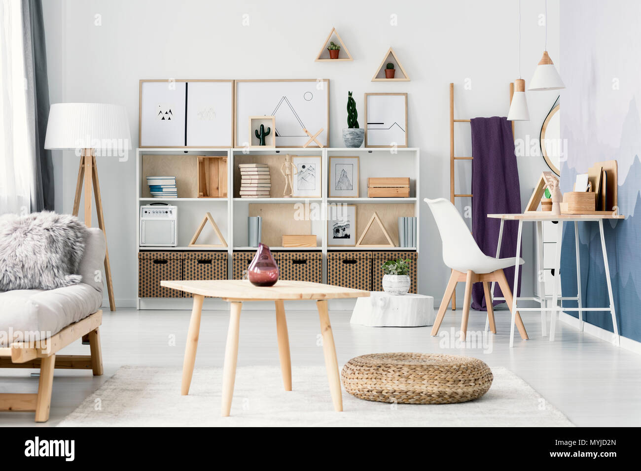 Pouf next to a wooden table in open space interior with white chair at desk and posters on the wall - Stock Image