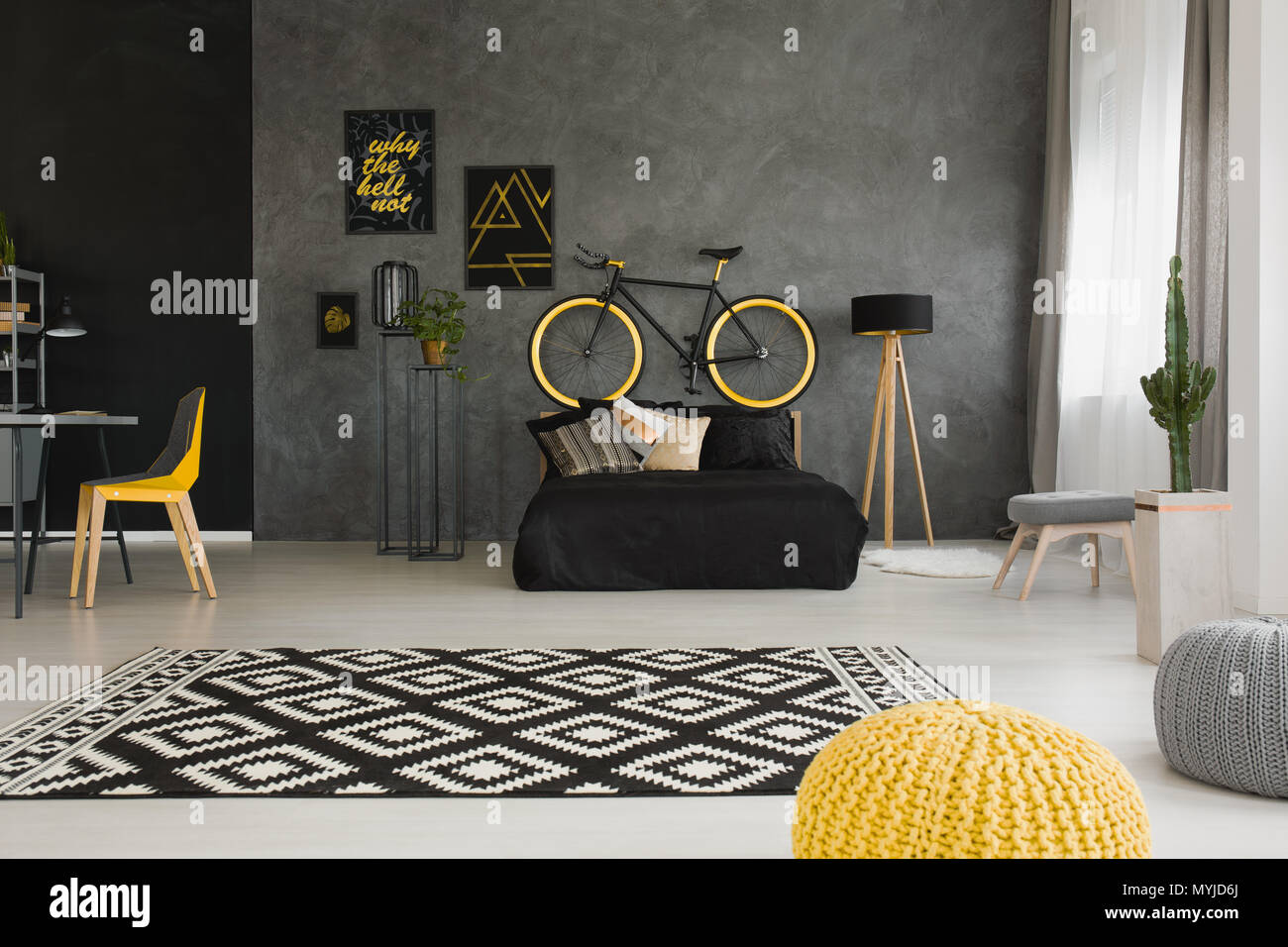 Bicycle above black bed in dark open space interior with pouf and yellow chair at desk. Real photo - Stock Image