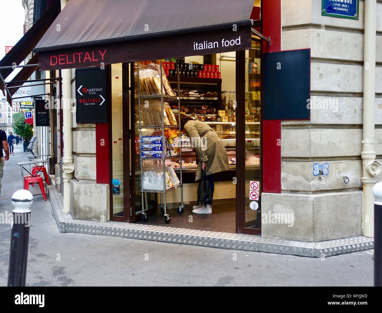 Woman wearing trench coat and white tennis shoes shopping in Deli Italy, an Italian food market in Montparnasse, Paris, France - Stock Image