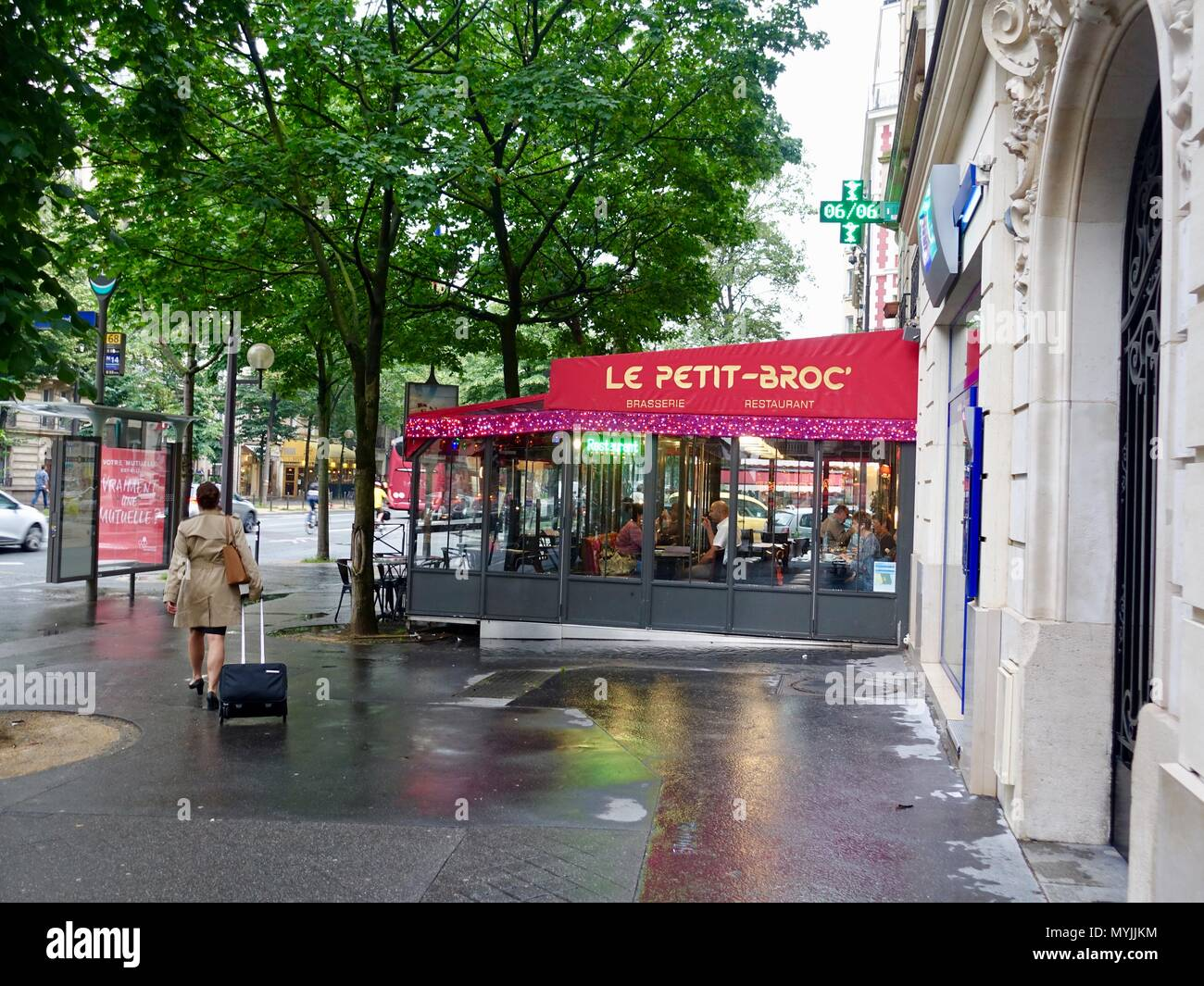 Woman wearing a trench coat and pulling a suitcase, walking down wet sidewalk in front of a restaurant, Montparnasse, Paris, France - Stock Image