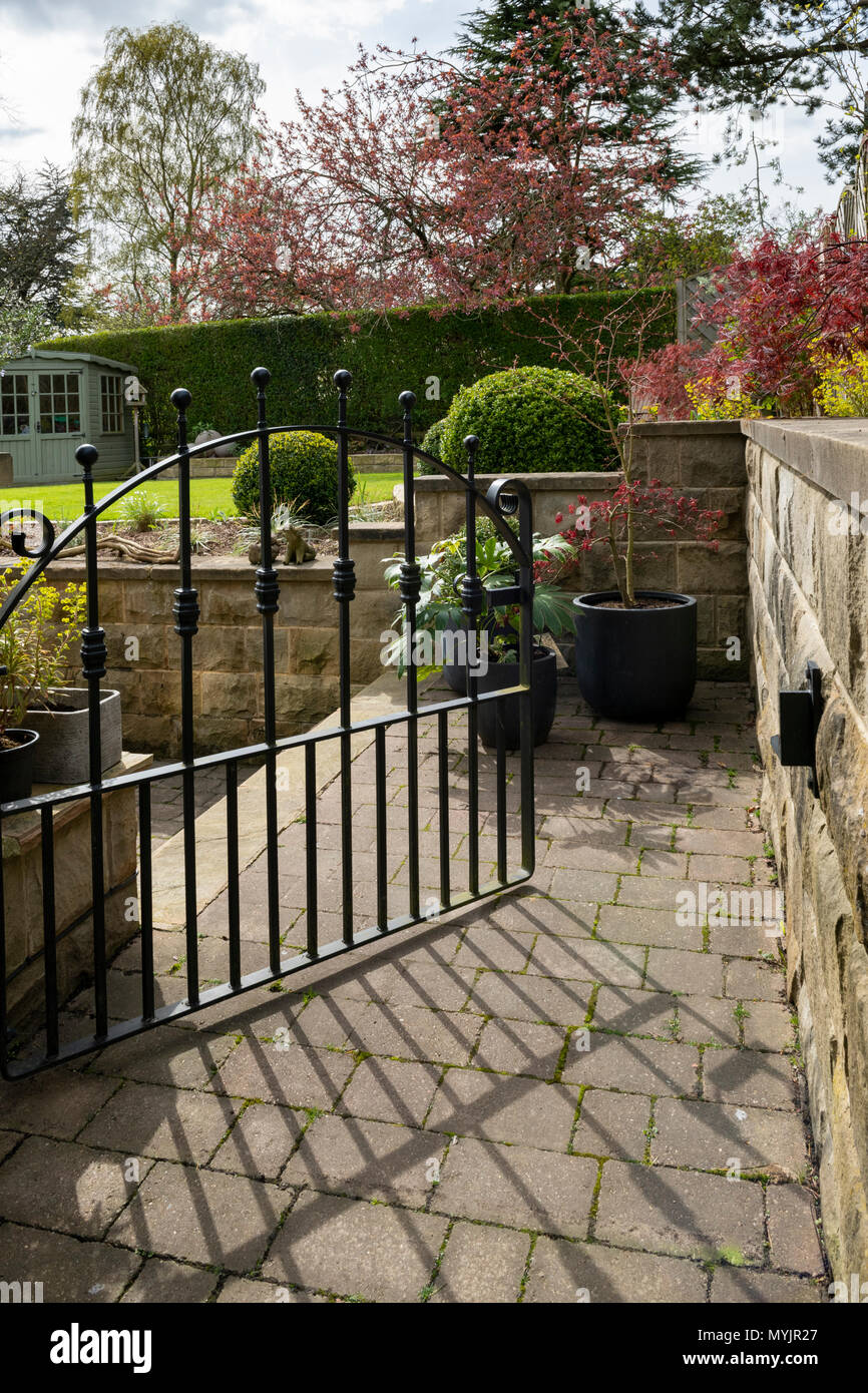 View through open gate to beautiful, landscaped, private garden with contemporary design, shrubs, box balls, path & neat lawn - Yorkshire, England, UK Stock Photo